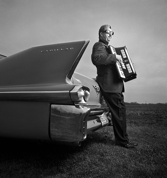 Lynn August with accordion and Cadillac
